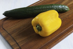 Cutting Board with yellow pepper and green cucumber. Fresh yellow pepper and cucumber lying on the kitchen chopping Board Stock Photo