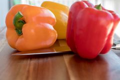 Close up of orange, yellow and red bell peppers. Cutting board with yellow pepper, red pepper, orange bell pepper and knife Royalty Free Stock Photos