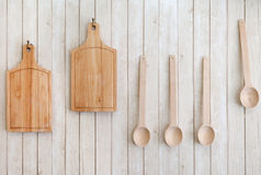 Cutting boards and wooden spoons hanging on the wall Stock Image