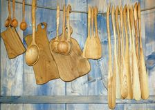 Cutting boards and wooden spoons hanging on the wall, tableware Royalty Free Stock Photo
