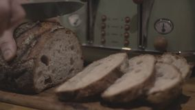 Cutting bread in the kitchen stock video footage