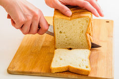 Cutting bread by knife. Woman cutting bread by knife on wooden board Royalty Free Stock Photography