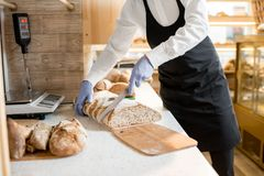 Cutting a bread in the store. Cutting fresh bread for selling in the store with bakery products Royalty Free Stock Photo