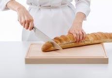Cutting bread on wooden board. Woman cutting bread on wooden board isolated on white closeup Stock Photos