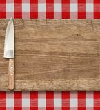 Cutting breadboard and kitchen knife. Cooking set over red gingham tablecloth. Royalty Free Stock Photo