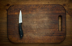 Cutting breadboard and knife overwooden background Royalty Free Stock Photos