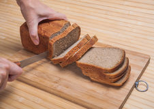 Cutting brown bread Royalty Free Stock Photo