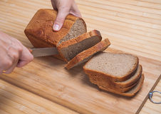 Cutting brown bread Royalty Free Stock Photography