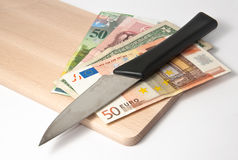 Cutting the budget. Several currency banknotes under a knife on a cutting board Royalty Free Stock Images