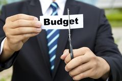 Cutting budget by business man. Businessman with scissors cutting label Budget Royalty Free Stock Images