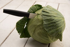 Cutting cabbage. A knife stuck inside a cabbage with the background of a white plank Stock Photo