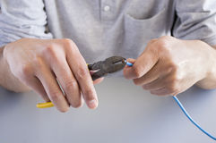 Cutting cable with pliers Royalty Free Stock Image
