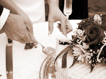 Cutting the cake - horizontal sepia. Bride and groom cutting the wedding cake Royalty Free Stock Images