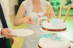Cutting Cake Tradition. Bride with slice of cake and groom with plate Stock Photography