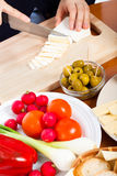 Cutting camembert cheese Stock Images