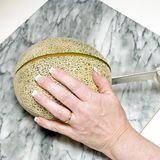 Cutting cantaloupe sequence 2. Sequential photos showing how to half cut a healthy orange whole cantaloupe with small knife on marble slab on kitchen counter and stock image