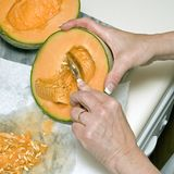 Cutting cantaloupe sequence 3. Sequential photos showing how to clean oout seeds and cut a healthy orange whole cantaloupe with small spoon on marble slab on royalty free stock photos