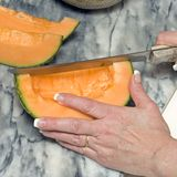 Cutting cantaloupe sequence 4. Sequential photos showing how to slice cut a healthy orange whole cantaloupe with small knife on marble slab on kitchen counter stock photo