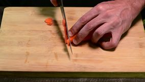 Cutting carrot with knife on the wood board stock footage