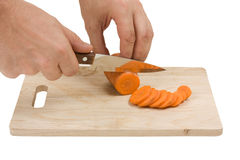 Cutting carrots on the board Royalty Free Stock Photos