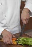 Cutting Carrots On för manlig kock träbräde arkivfoto