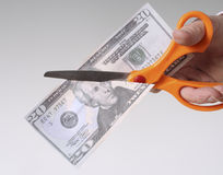 Cutting Cash With Scissors. Male hand with scissors cutting a twenty dollar bill in half Stock Images