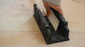 Cutting a ceiling molding in miter box. Hands of a craftsman cutting a white ceiling molding with hand saw using a plastic miter box stock footage