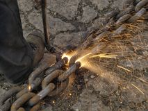 Cutting a chain. Close-up of a iron-worker producing a spray of sparks while cutting a steel chain with a cutting torch Royalty Free Stock Image