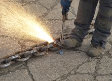 Cutting a chain. Close-up of a iron-worker producing a spray of sparks while cutting a steel chain with a cutting torch Royalty Free Stock Photo