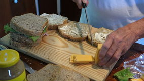 Cutting cheddar cheese for sandwiches at Mac's pizzeria stock video footage
