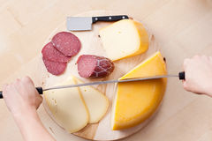 Cutting cheese and sausage Royalty Free Stock Images