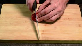 Cutting cherry tomato with knife on the wood board stock footage