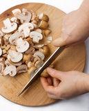 Cutting the chestnut mushrooms into thin slice Royalty Free Stock Photo