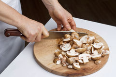 Cutting the chestnut mushrooms into thin slice Stock Images