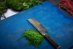 Cutting chives in restaurant kitchen Stock Photography