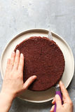 Cutting a chocolate sponge cake into layers Royalty Free Stock Image