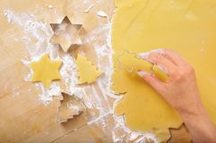 Cutting Christmas cookies. Female hand holding a cookie cutter above flattened dough for baking.  Additional cookie cutters and shapes sitting to the left Stock Image