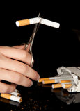 Cutting a cigarette stock photography