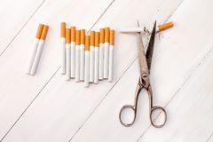 Cutting cigarettes by scissors. Anti smoking or quit smoking concept Royalty Free Stock Photo