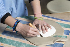 Cutting the clay to shape Stock Photo