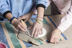 Cutting the clay to shape Stock Photos