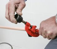 Cutting a copper pipe with a pipe cutter. Plumber cutting a copper pipe with a pipe cutter stock photography