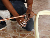 Cutting a copper pipe with a pipe cutter Stock Images