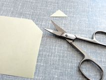 Cutting corners idiom. Briticism hand takes sheet of paper and cutting corners by scissors doing something so easily and cheaply as possible royalty free stock image
