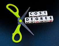 Cutting cost of a degree. Text ' cost ' and ' degree ' in uppercase letters inscribed on small white cubes together with scissors to indicate cutting, dark Stock Photography