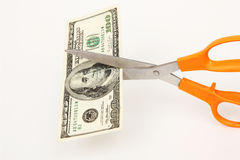 Cutting Costs. Scissors cutting a hundred dollar bill Stock Photo