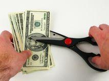 Cutting Costs - Scissors and Dollars Royalty Free Stock Images