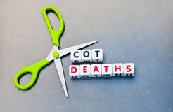 Cutting cot deaths. Scissors against text ' cot deaths ' in uppercase letters inscribed on small white cubes, gray background Royalty Free Stock Images
