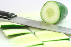 Cutting cucumber. Sliced up cucumber with a kitchen knife stock photo