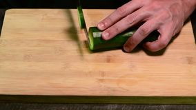 Cutting cucumber with knife stock footage